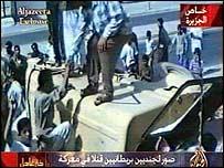 Armed civilians climb over the wrecked vehicle on al-Jazeera TV