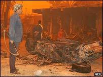 Iraqi militiaman stands next to wrecked car in market