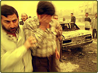 An Iraqi comforts a friend at the site hit by two US-British missiles in Baghdad 26 March 2003