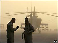 US servicemen stand in front of Apache helicopters in Kuwait