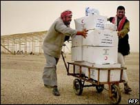 Two Iraqi men push a trolley loaded with aid supplies