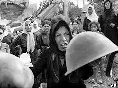 Palestinian woman brandishes helmets during a memorial service in Beirut September 27, 1982, claiming they belonged to some of the killers