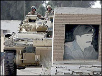 British tank knocks down wall with Saddam Hussein's picture