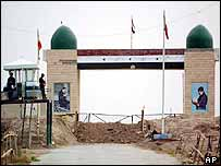 Iranian soldiers, left, guard the closed border of Shalamcheh with Iraq, about 15 miles East of Iraq's second-largest city of Basra