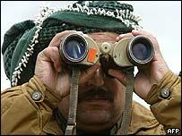 Kurdish guerrilla fighter scanning abandoned Iraqi positions near Kirkuk