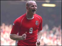 Wales striker John Hartson celebrates after scoring Wales' third goal