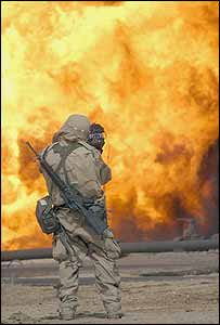 Spc. Bernard S. Wiess, a journalist assigned to the 22nd Mobile Public Affairs Detachment, films an oil fire in Iraq
