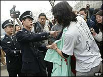 An anti-war protester is confronted in Beijing