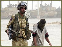 A Royal Marine Commando escorts an Iraqi POW