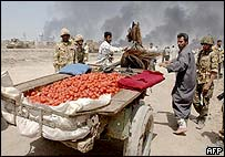 Two Iraqi men handle a horse-drawn cart full of tomatoes across a checkpoint on the outskirts of Basra