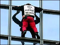 "Frenchman Alain Robert climbs office building in Paris with ""No War"" sign on his tee-shirt"