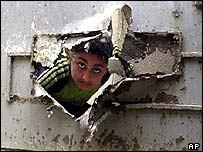 Boy in Baghdad peers through hole made by shrapnel in a door in Baghdad