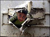 Boy in Baghdad peers through hole made by shrapnel in a door in Baghdad