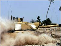 A British Challenger II tank raises a cloud of dust as it travel through a location near Basra in southern Iraq