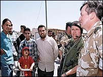 A British soldier talks to locals in Umm Qasr