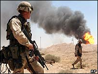 US soldiers on guard duty near a burning oil well in Iraq