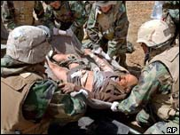 Injured Iraqi men lay on the ground as they wait to be treated by US troops outside Baghdad