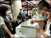 Thai Airway employees wear masks as they man their counter at Bangkok International Airport
