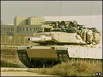 A US tank moves across the runway with the airport buildings in the background