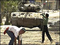 Palestinian children throw stones at a tank in Jenin on Friday