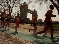 Runners plod through the shadow of Tower Bridge