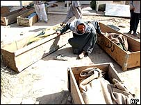 An Iraqi man surrounded by coffins of his family
