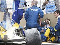 Fernando Alonso is attended by medics after his crash at Interlagos