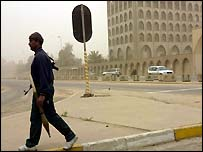 An Iraqi militiaman walks near the Ministry of Information