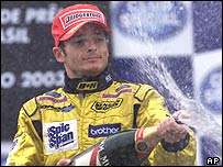 Giancarlo Fisichella looks rueful as he sprays the champagne on the podium at the Brazilian Grand Prix