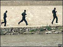 Iraqi troops run along the Tigris river as US troops advance