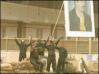 Iraqi soldiers raise a victory sign below a portrait of Saddam Hussein