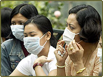 Hong Kong domestic workers gather together on their day off, wearing masks to protect against the killer pneumonia.