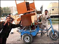 Two Iraqis with a tricycle loaded with furniture