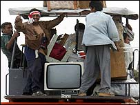 Iraqi men wave from a truck as they leave the centre of Basra, southern Iraq, after looting shops and houses