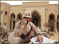 1st Brigade troops communicate with each other after taking over one of Saddam Hussein's palaces