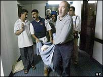 Journalists carry wounded colleague through the Palestine Hotel