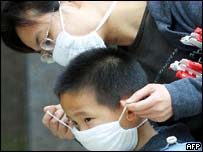 A woman puts on a surgical mask for her son as they leave their home in Guangzhou