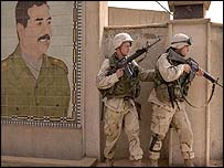 US soldiers in Baghdad, standing next to a mural depicting Saddam Hussein