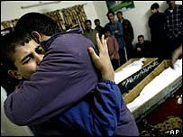 Member of the Amer family weep over the coffins of relatives killed in the Shula market bombing
