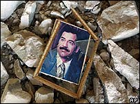 A shattered picture of Saddam Hussein lies in a pile of rubble in Basra