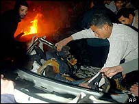 Palestinians inspect wreckage of car hit by missiles