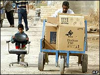 A father and son wheel looted goods though a Baghdad street