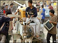 People in Baghdad load a cart with looted goods