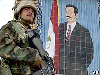US marine beside mural of Saddam Hussein
