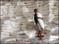 Young Iraqi boy holding a sack of sugar from a warehouse