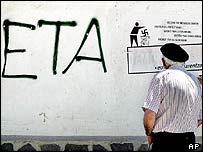 A man reads graffiti reading in several languages, ETA, Freedom For The Basque Country, in Leiza, northern Spain