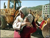 Sisters comfort each other near their ruined home in Thenia