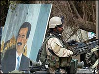 U.S. Special Forces take a position in a Baghdad intersection, near a portrait of Saddam Hussein