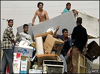 Iraqi men load looted electrical equipment onto a truck in Baghdad