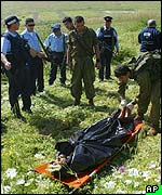 Israeli soldiers and policemen examine the body of one of two Palestinian gunmen who infiltrated into an Israeli military training base
